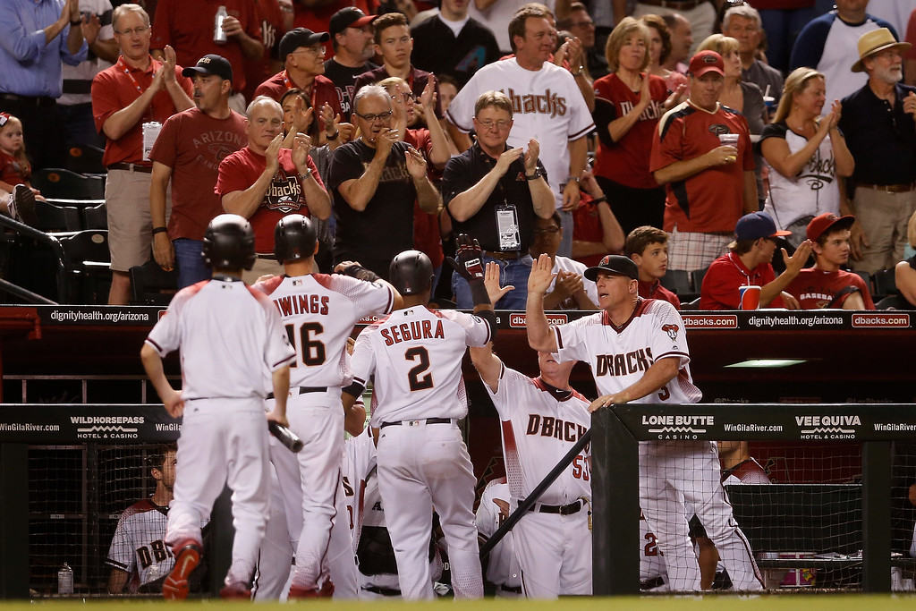 . PHOENIX, AZ - APRIL 04:  Manager Chip Hale #3 of the Arizona Diamondbacks high fives Jean Segura #2 and Chris Owings #16 after scoring against the Colorado Rockies during the fifth inning of the MLB opening day game at Chase Field on April 4, 2016 in Phoenix, Arizona.  (Photo by Christian Petersen/Getty Images)