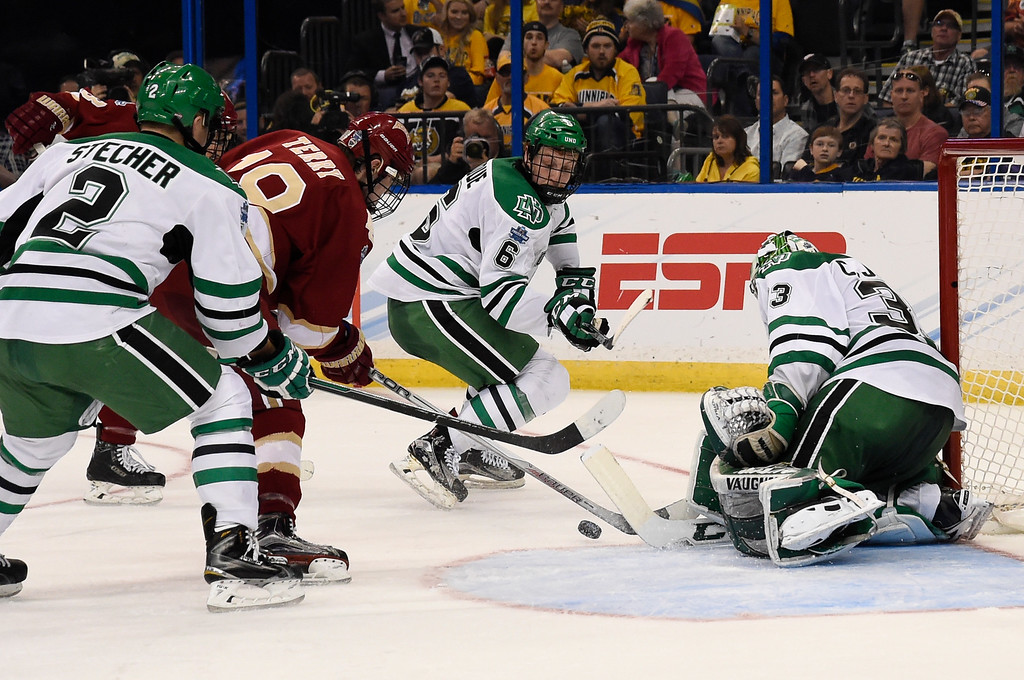 . TAMPA, FL - APRIL 07: Denver Pioneers forward Troy Terry (19) tries to get a shot off on North Dakota Fighting Hawks goalie Cam Johnson (33) during the second period in the NCAA Tournament - National Semifinals April 7, 2016 at Amalie Arena. (Photo By John Leyba/The Denver Post)