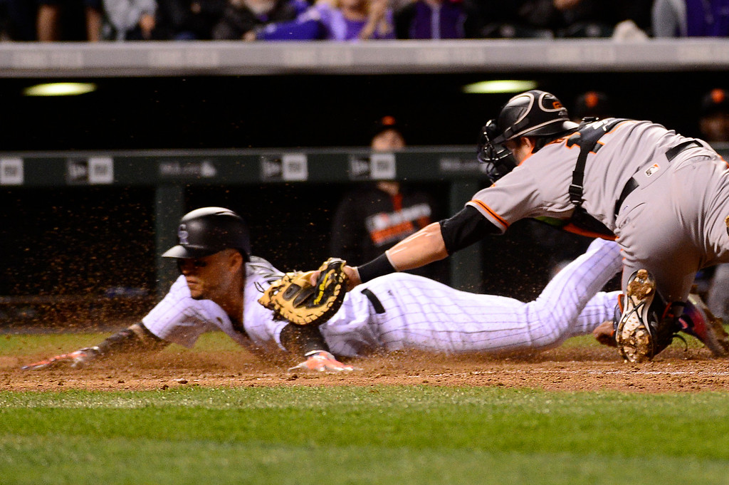 . DENVER, CO - APRIL 12: San Francisco Giants catcher Trevor Brown (14) tags out Colorado Rockies right fielder Carlos Gonzalez (5) as he tries to slide into home during the fifth inning at Coors Field on April 12, 2016 in Denver, Colorado. (Photo by Brent Lewis/The Denver Post)
