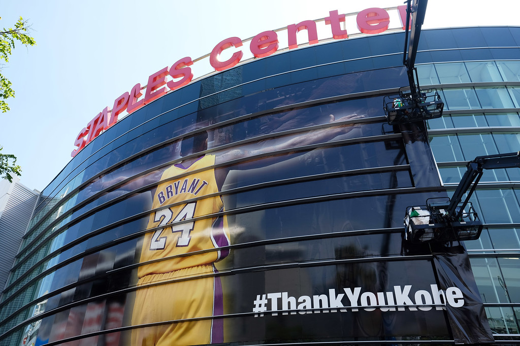 . Workers wrap Staples Center in a giant banner congratulating Kobe Bryant before his last NBA basketball game, a contest against the Utah Jazz, in downtown Los Angeles Wednesday, April 13, 2016. Many of Bryant\'s fans - even some of the adults - have never known Los Angeles without him. I\'s a feeling they\'re about to have to get used to as fans celebrate his final night as a Laker. (AP Photo/Richard Vogel)