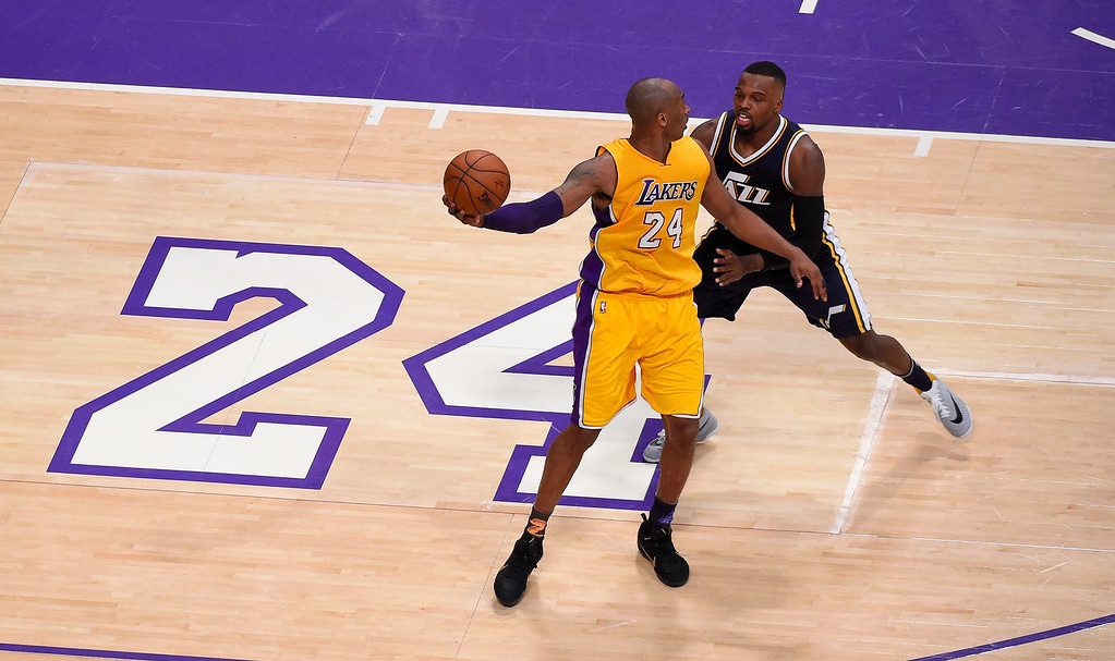 . Los Angeles Lakers forward Kobe Bryant, left, works against Utah Jazz guard Shelvin Mack during the first half of an NBA basketball game, Wednesday, April 13, 2016, in Los Angeles. (AP Photo/Mark J. Terrill)
