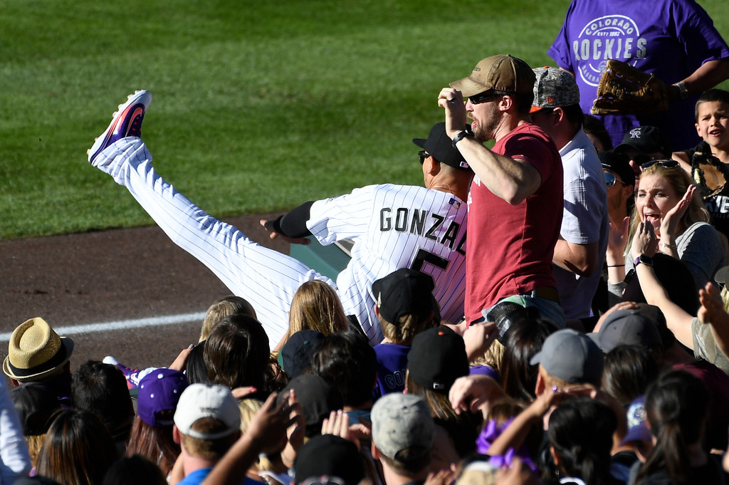 . DENVER, CO - APRIL 24: Colorado Rockies right fielder Carlos Gonzalez (5) tracks down a high fly ball in foul territory hit by Los Angeles Dodgers catcher Yasmani Grandal (9) in the 9th inning against the Colorado Rockies April 24, 2016 at Coors Field.  Gonzalez made an attempt to catch the ball and flipped in to the stands and missed the ball. (Photo By John Leyba/The Denver Post)