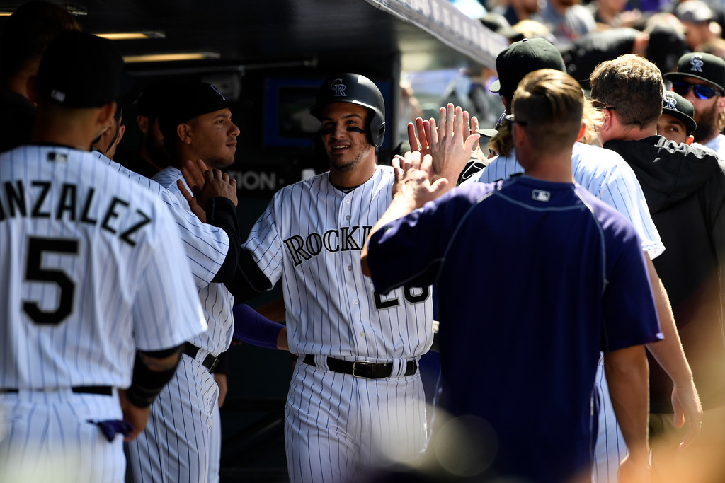 . DENVER, CO - APRIL 24: Colorado Rockies third baseman Nolan Arenado (28) gets high fives in the dugout after scoring on a hit by Colorado Rockies right fielder Gerardo Parra (8) in the second inning against the Los Angeles Dodgers April 24, 2016 at Coors Field. (Photo By John Leyba/The Denver Post)