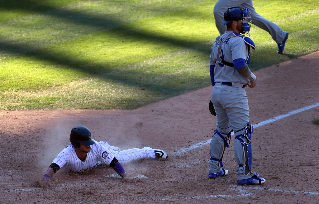 . DENVER, CO - APRIL 24: Colorado Rockies shortstop Cristhian Adames (18) slides in at home plate safely to score on a Colorado Rockies right fielder Carlos Gonzalez (5) single in the 8th inning against the Los Angeles Dodgers April 24, 2016 at Coors Field. (Photo By John Leyba/The Denver Post)
