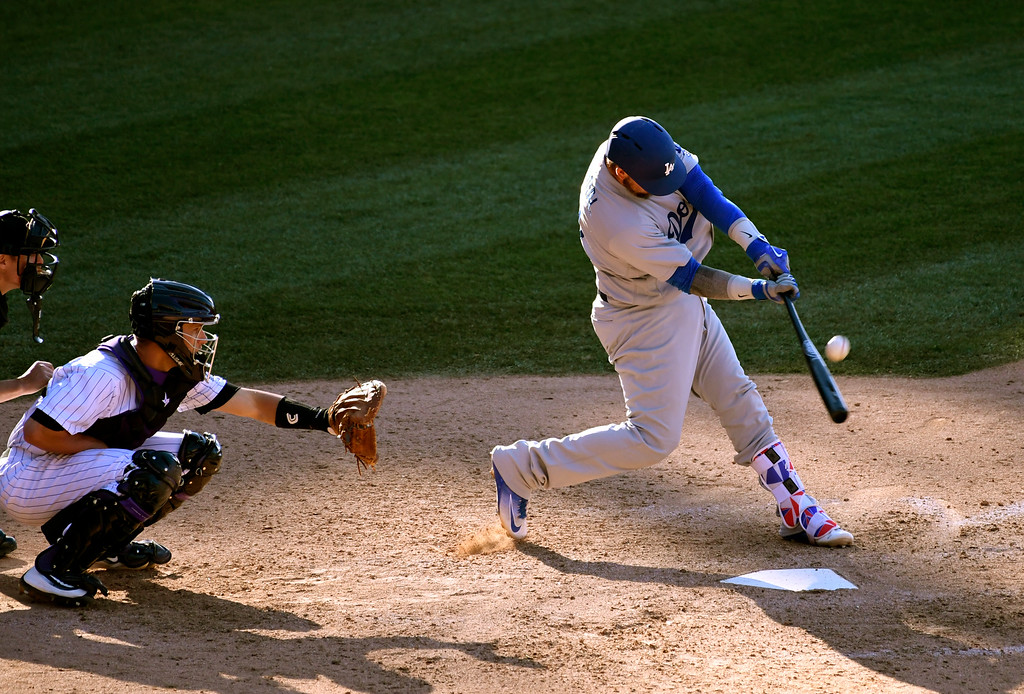 . DENVER, CO - APRIL 24: Los Angeles Dodgers catcher Yasmani Grandal (9) hits a high foul ball down the right field line in the 9th inning against the Colorado Rockies April 24, 2016 at Coors Field. Colorado Rockies right fielder Carlos Gonzalez (5) gave chase in an attempt to catch the ball and flipped in to the stands. (Photo By John Leyba/The Denver Post)