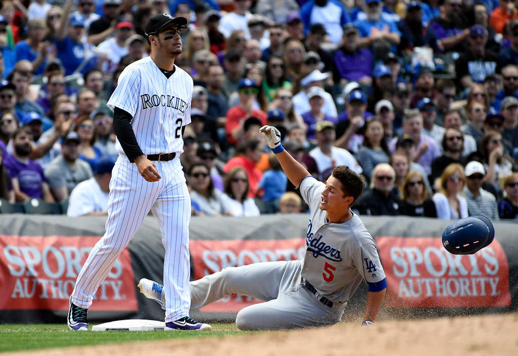 . DENVER, CO - APRIL 24: Los Angeles Dodgers shortstop Corey Seager (5) slides in to third safely as he hits a triple to right field as Colorado Rockies third baseman Nolan Arenado (28) looks on in the third inning April 24, 2016 at Coors Field. (Photo By John Leyba/The Denver Post)