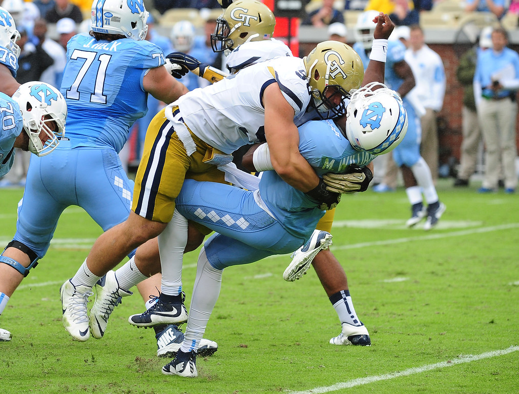 . Marquise Williams #12 of the North Carolina Tar Heels takes a hit from Adam Gotsis #96 of the Georgia Tech Yellow Jackets on October 3, 2015 in Atlanta, Georgia. Gotsis would be penalized and ejected from the game for the hit. Photo by Scott Cunningham/Getty Images)