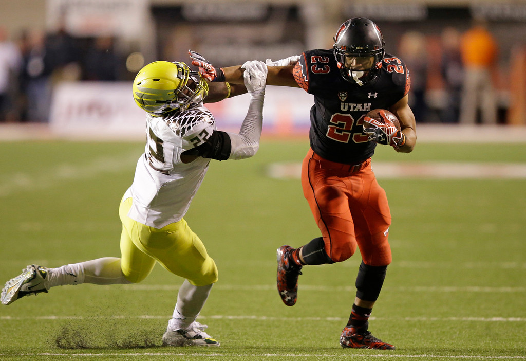 . Oregon linebacker Derrick Malone (22) attempts to make a tackle as Utah running back Devontae Booker (23) carries the ball in the second quarter during an NCAA college football game Saturday, Nov. 8, 2014, in Salt Lake City. (AP Photo/Rick Bowmer)