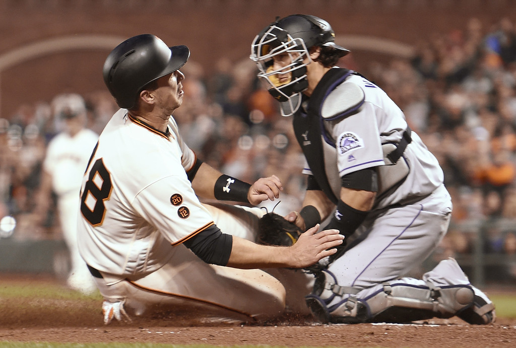 . SAN FRANCISCO, CA - MAY 05:  Buster Posey #28 of the San Francisco Giants gets tagged out at home plate while colliding with catcher Tony Wolters #14 of the Colorado Rockies in the bottom of the third inning at AT&T Park on May 5, 2016 in San Francisco, California.  (Photo by Thearon W. Henderson/Getty Images)