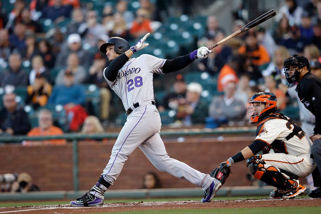 . Colorado Rockies\' Nolan Arenado (28) follows through on a 2-run home run against the San Francisco Giants during the first inning of a baseball game Thursday, May 5, 2016, in San Francisco. (AP Photo/Marcio Jose Sanchez)