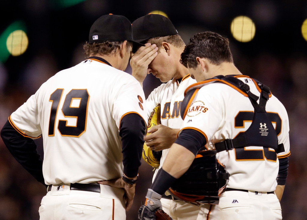 . San Francisco Giants starting pitcher Matt Cain, center, gets a visit to the mound from pitching coach Dave Righetti (19) and catcher Buster Posey after Cain gave up a double to Colorado Rockies\' Carlos Gonzalez during the fifth inning of a baseball game Thursday, May 5, 2016, in San Francisco. (AP Photo/Marcio Jose Sanchez)