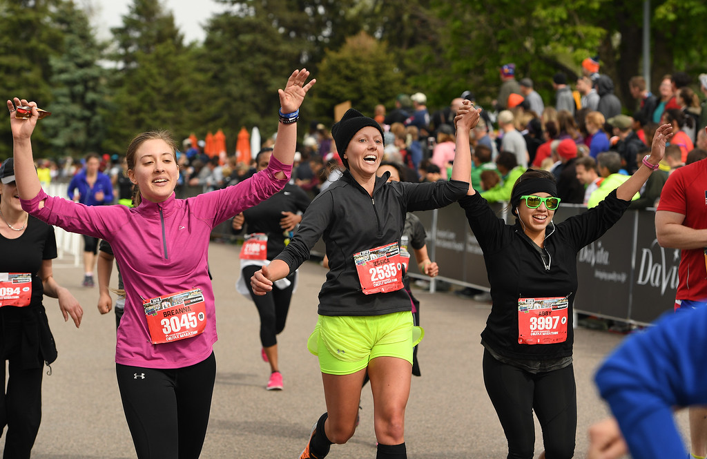 . DENVER, CO - MAY 15: Runners Breanna Stranges, left, Jessica Whittet, in the middle, her friend Abby Molina, right, are exuberant as they cross the finish line of the Colfax Half Marathon during the 11th annual Colfax Half Marathon on May 15, 2016 in Denver, Colorado.  Thousands of runners took part in the annual springtime race which included a marathon, a marathon relay,  a half marathon and the urban 10 miler.  (Photo by Helen H. Richardson/The Denver Post)