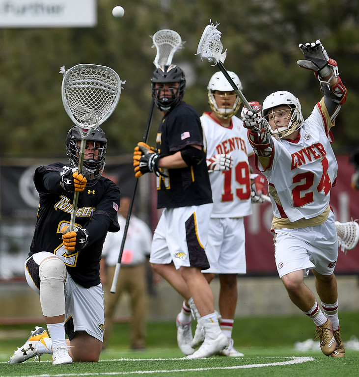. DENVER, CO - MAY 15:  Tyler White (2) of the Towson gets rid of the ball after saving a shot as  Connor Donahue (24) of the Denver defends during the fourth quarter of Towson\'s 10-9 win. University of Denver hosted Towson University in an NCAA tournament game on Sunday, May 15, 2016. (Photo by AAron Ontiveroz/The Denver Post)
