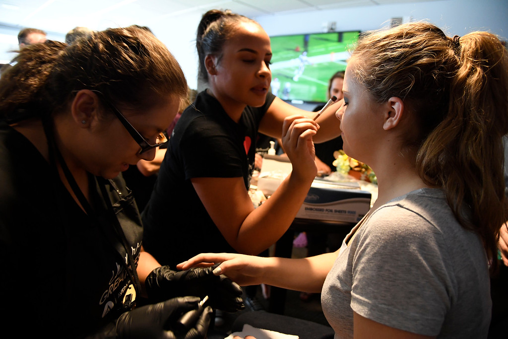 . Linda Segmental (L) and Angela Roelle help Ellie Lindo, 14, with her makeup as she gets ready for prom. Teens get their makeup, hair and nails done before prom night May 13, 2016 at Sports Authority Field at Mile High. The teen patients had a treat as they got to meet with Denver Broncos quarterback Mark Sanchez who was on hand to greet them. Some of the teens missed their own prom due to illness and just couldn\'t attend. Childrens Hospital hosted the Night of Champions gala. (Photo By John Leyba/The Denver Post)