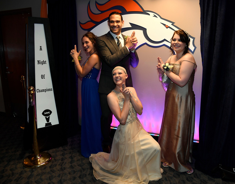 . Denver Broncos quarterback Mark Sanchez poses for a photo with Karissa Harves, 17, (L) Grace Jackson, 18, (on her knee) and Bailey Williams, 18,  during a Night of Champions prom. Teens got their makeup, hair and nails done before prom night May 13, 2016 at Sports Authority Field at Mile High. Some of the teens missed their own prom due to illness and just couldn\'t attend. Childrens Hospital hosted the Night of Champions gala. (Photo By John Leyba/The Denver Post)