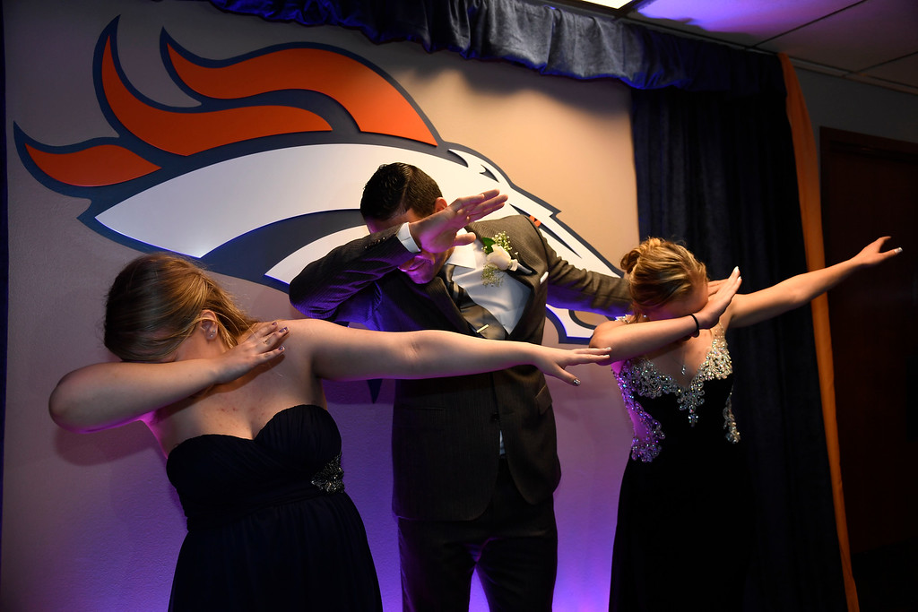 . Denver Broncos quarterback Mark Sanchez dabs with Hadley Hull, 15, and Sarah Petersen, 17, during a Night of Champions prom. Teens got their makeup, hair and nails done before prom night May 13, 2016 at Sports Authority Field at Mile High. Some of the teens missed their own prom due to illness and just couldn\'t attend. Childrens Hospital hosted the Night of Champions gala. (Photo By John Leyba/The Denver Post)