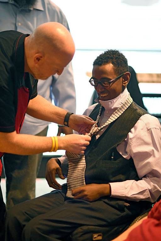 . Million Anteneh, 26, gets his tie put on by Michael Dunkle before prom night May 13, 2016 at Sports Authority Field at Mile High. The teen patients had a treat as they got to meet with Denver Broncos quarterback Mark Sanchez who was on hand to greet them. Some of the teens missed their own prom due to illness and just couldn\'t attend. Childrens Hospital hosted the Night of Champions gala. (Photo By John Leyba/The Denver Post)