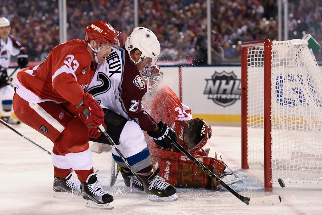 . DENVER, CO - FEBRUARY 26: Colorado Avalanche Claude Lemieux (22) takes a shot on Manny Legace (34) as Detroit Red Wings  Kris Draper (33) defends on the play during the third period February 26, 2016 at Coors Field. (Photo By John Leyba/The Denver Post)