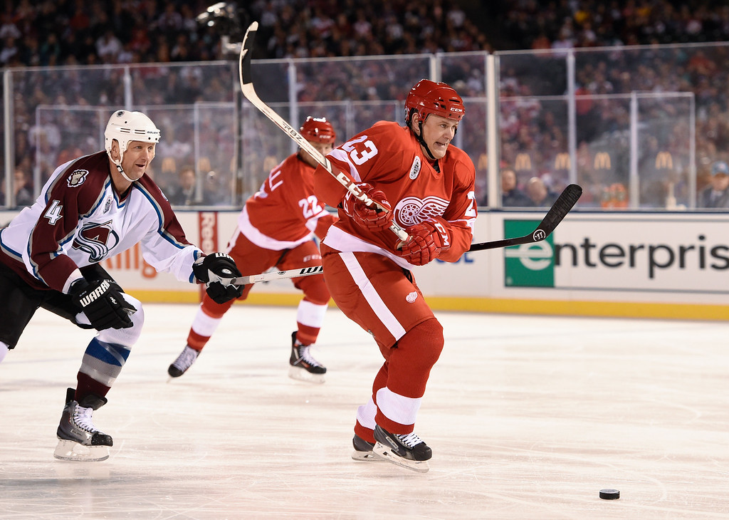 . DENVER, CO - FEBRUARY 26:  Detroit Red Wings Stacy Roest (23) skates down the puck as Colorado Avalanche Rob Blake (4) chases after during the second period February 26, 2016 at Coors Field. (Photo By John Leyba/The Denver Post)