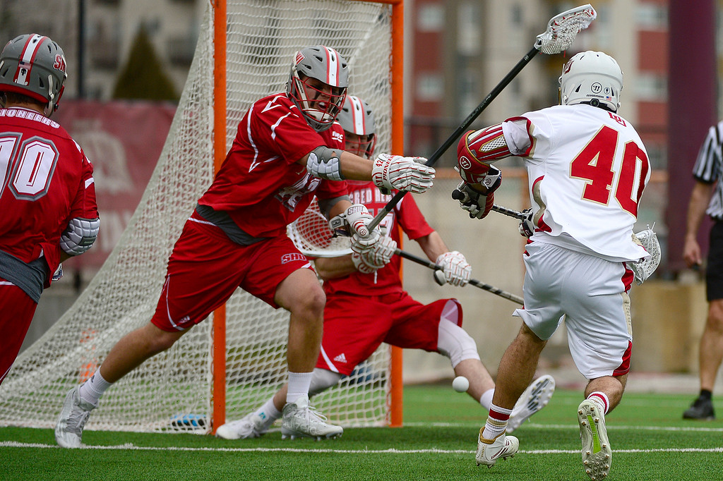 . Denver Connor Cannizzaro (40) sneaks a shot around the defense of  Sacred Heart Owen Thomson (42) and under the legs of Sacred Heart Mitch Hall (23) at the University of Denver on February 27, 2016 in Denver, Colorado. Denver drafted Sacred Heart 18-7.  (Photo by Brent Lewis/The Denver Post)