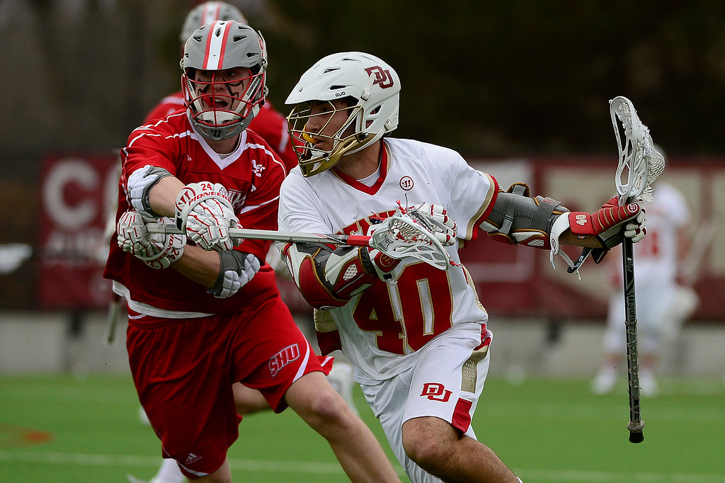 . Sacred Heart Ryan O\'Donoghue (24) tries to guard Denver Connor Cannizzaro (40) during the second quarter at the University of Denver on February 27, 2016 in Denver, Colorado. Denver drafted Sacred Heart 18-7.  (Photo by Brent Lewis/The Denver Post)