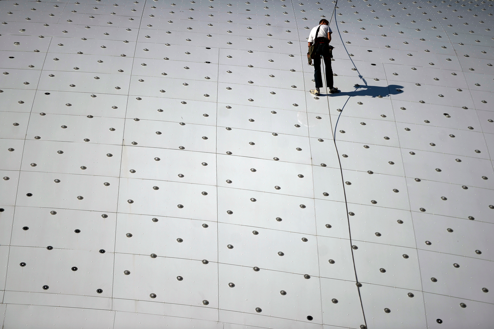 . A worker climbs the roof of the arena before the first period of men\'s hockey action at Bolshoy arena. Sochi 2014 Winter Olympics on Saturday, February 15, 2014. (Photo by AAron Ontiveroz/The Denver Post)