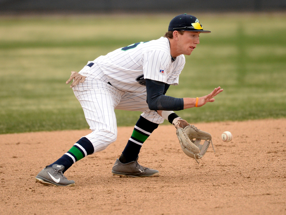 . ThunderRidge shortstop Brody Westmoreland scooped up a ground ball in the second inning. The Mountain Vista High School baseball team blanked ThunderRidge 3-0 Wednesday afternoon, April 16, 2014. (Photo by Karl Gehring/The Denver Post)