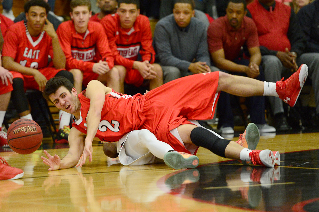 . CENTENNIAL, CO - MARCH 2: Jack Buckmelter (2) of Denver East falls over Elijah Wilson (11) after being fouled during the fourth quarter at Eaglecrest High School on March 2, 2016 in Centennial, Colorado. Eaglecrest defeated Denver East 56-46. (Photo by Brent Lewis/The Denver Post)