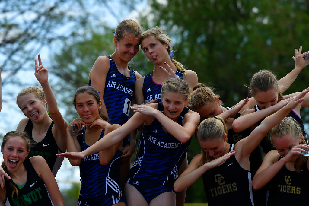 . LAKEWOOD, CO - May 19: Air Academy 4A 4x800 meter relay champions Katie Rainsberger, top left, and teammate Kayla Wiitala, top right,  Maria Mettler, below Rainsberger, and Lilliana Hamilton, below Wiitala, along with the second place team from Niwot, bottom left, and third place team from Canon City, bottom right,  strike poses on the medals stand at the Colorado State High School Track and Field Championships at Jeffco Stadium May 19, 2016. (Photo by Andy Cross/The Denver Post)