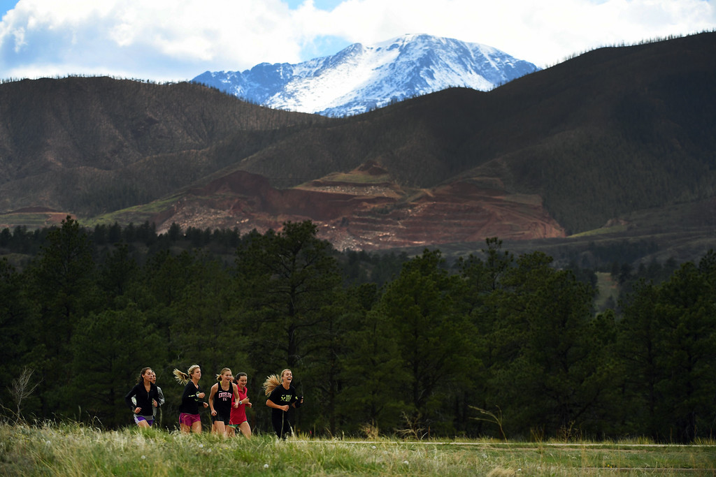 . COLORADO SPRINGS, CO - MAY 10:  Runner Katie Rainsberger, right, warms up with teammates with Pikes Peak at their backdrop during her afternoon work out at Air Academy High School on the Air Force Academy campus at  on May 10, 2016 in Colorado Springs, Colorado. (Photo by Helen H. Richardson/The Denver Post)
