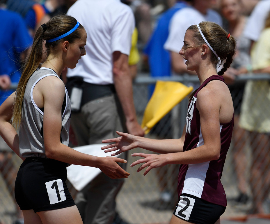 . Brie Oakley, Grandview, left, is greeted by competition Madison Mooney, Horizon, after the 1600 meter run final at the Colorado Track and Field State Championships at Jeffco Stadium May 21, 2016. Mooney clipped Oakley on a turn causing her to fall, Mooney crossed the finish line first, but was later disqualified, giving the victory to Oakley. (Photo by Andy Cross/The Denver Post)