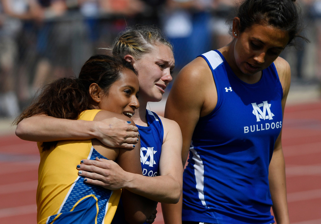 . Kayla Pinnt, Moffat County, center, hugs competitor Jazmin Contreras, Roaring Fork, left, walking off the track with teammate Selena Hernandez, right, after Pinnt won the 3A 100 meter dash final at the Colorado Track and Field State Championships at Jeffco Stadium May 21, 2016. (Photo by Andy Cross/The Denver Post)