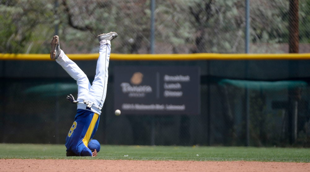 . Dove Creek Jordan Ernst (8) goes head over heals as he can\'t make a catch on a fly by by Caliche Seth Miller (3) in the 7th inning of the Championship game May 15, 2014 at All-Star Park. Caliche defeated Dove Creek 17-1 for the title. (Photo by John Leyba/The Denver Post)