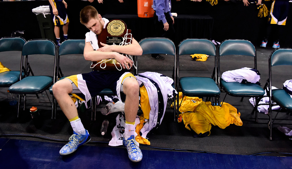. CS Christian Lions Pete Wilson (22) holds the  championship trophy alone on the empty bench after the Championship 3A game at the Coliseum.  Christian defeated Alamos 57-43 for back to back championships. (Photo By John Leyba/The Denver Post)
