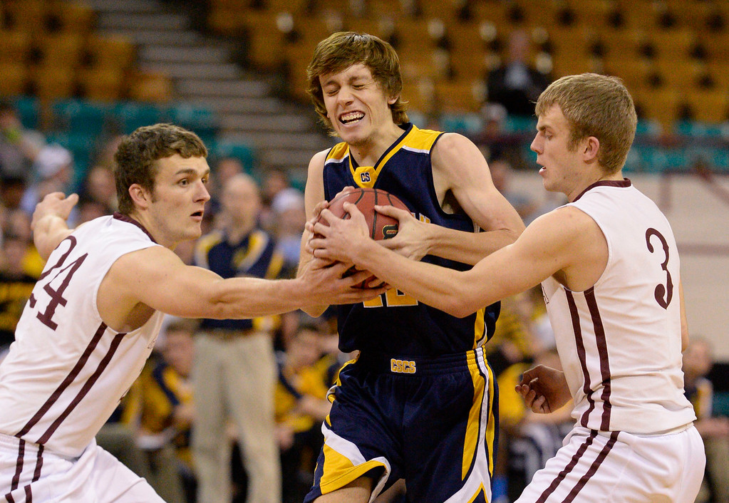 . Alamosa Mean Moose Ryan Brubacher (24) and Clayton Brubacher (3) try to rip the ball away from CS Christian Lions Trey Nielsen (12) during the Championship 3A game at the Coliseum. (Photo By John Leyba/The Denver Post)