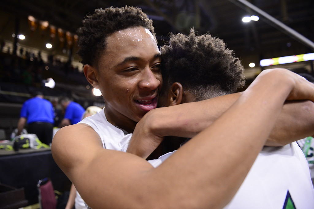. Jervae Robinson (0) of Overland Trailblazers hugs Reggie Gibson (1) of Overland Trailblazers after defeating Eaglecrest Raptors at the Coors Events Center on March 12, 2016 in Boulder, Colorado. Overland Trailblazers defeated Eaglecrest Raptors 66-56 to win the Colorado State 5A Basketball Championship.  (Photo by Brent Lewis/The Denver Post)