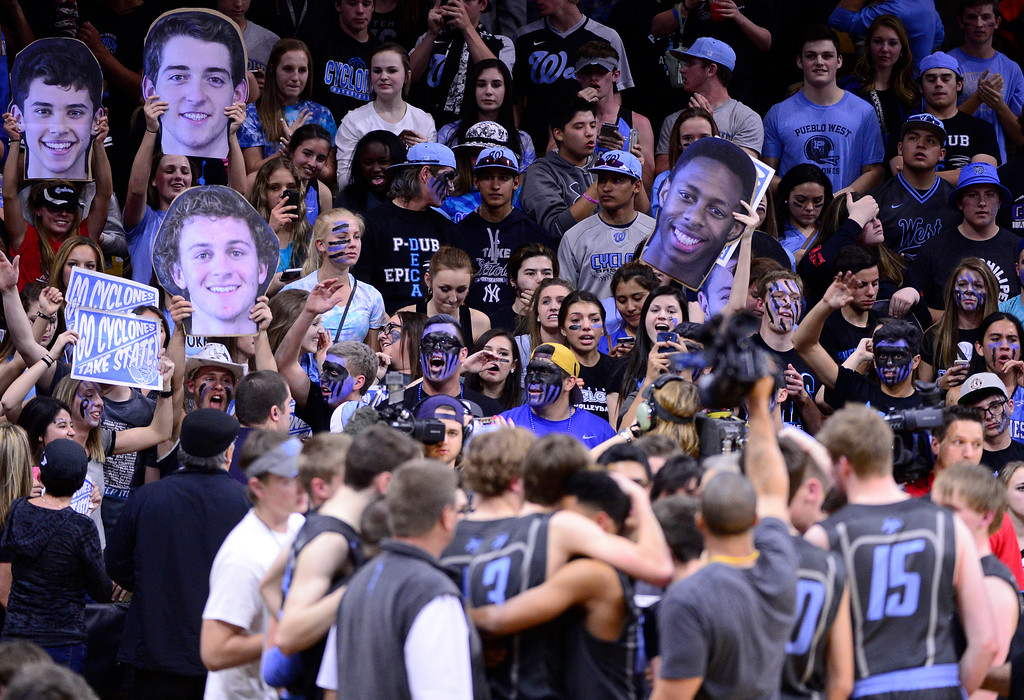 . Pueblo West Cyclones fans hold signs while the starting players hug after coming off the court during the fourth quarter at the Coors Events Center on March 12, 2016 in Boulder, Colorado. Pueblo West Cyclones defeated Valor Christian Eagles 70-51 to win the Colorado State 4A Boys Championship. (Photo by Brent Lewis/The Denver Post)