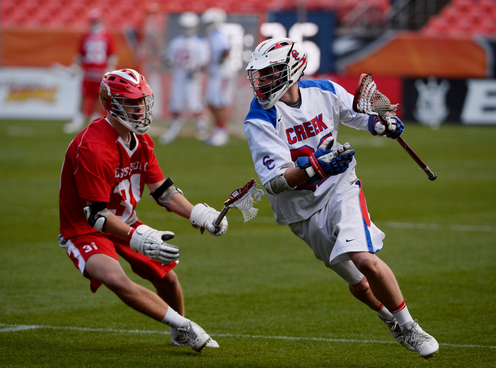 . Michael Morean, right, Cherry Creek, midfielder, tries to get around Regis defender, Joey Soran, left, in the first half of the Colorado State 5A boys lacrosse championship at Sports Authority Field at Mile High Saturday evening, May 17, 2014. Regis won 14-7.  (Photo By Andy Cross / The Denver Post)