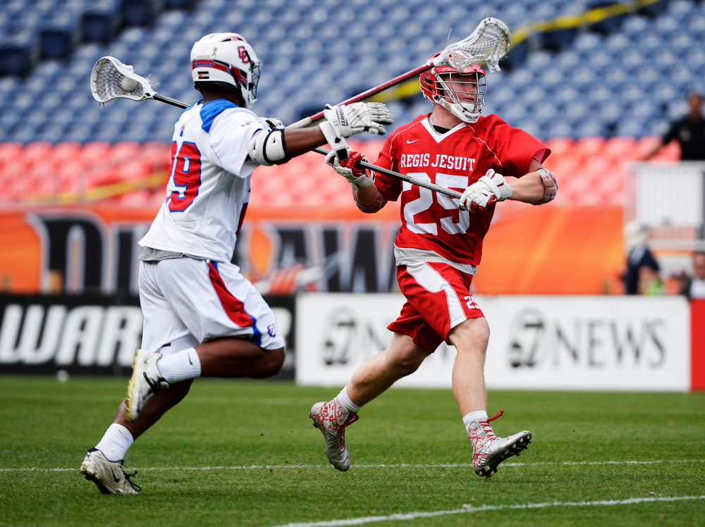 . Regis defenseman, Conner Shea, right, gets down field against the defense of Steve O\'Malley, during the Colorado State 5A boys lacrosse championship at Sports Authority Field at Mile High Saturday evening, May 17, 2014. (Photo By Andy Cross / The Denver Post)
