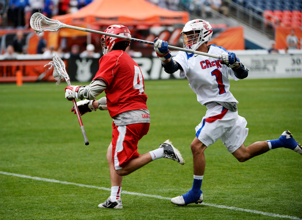 . Regis midfielder, Chet Dunstan, left, gets past Cherry Creek defender, Zach Yoshioka, during the Colorado State 5A boys lacrosse Championship at Sports Authority Field at Mile High Saturday evening, May 17, 2014. (Photo By Andy Cross / The Denver Post)