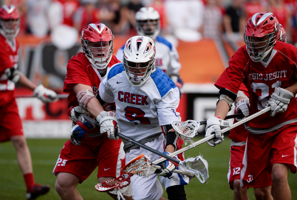 . Cherry Creek attacker, Ryan Arthur, center, gets swarmed by Regis defenders, Conner Shea, left, and Joey Soran, right, in the forest half of play during the Colorado State 5A boys lacrosse Championship at Sports Authority Field at Mile High Saturday evening, May 17, 2014. Regis went on to win 14-7. (Photo By Andy Cross / The Denver Post)