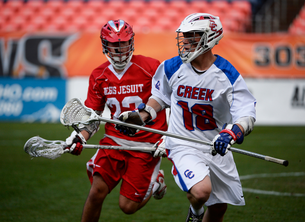. Cherry Creek defenseman, Charlie Fay, right, heads down field against Ryan Bechter, Regis, in the first half during the Colorado State 5A boys lacrosse Championship at Sports Authority Field at Mile High Saturday evening, May 17, 2014. (Photo By Andy Cross / The Denver Post)