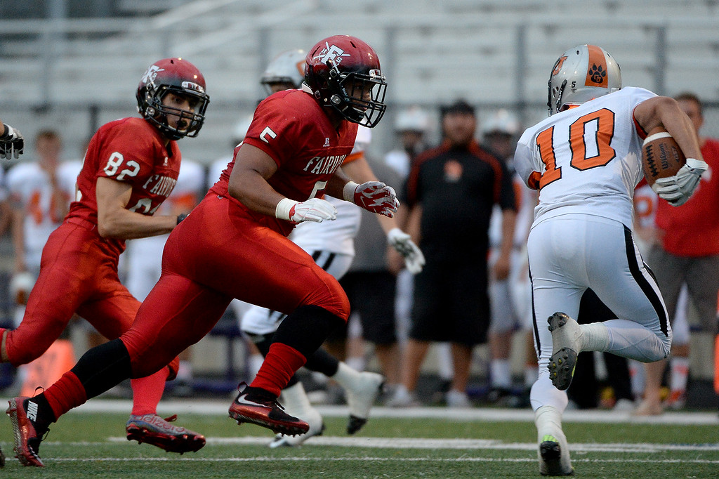 . Carlo Kemp gives chase as Grand Junction ball carrier Austin Taylor looks for room to run on Friday, September 5, 2015. (Photo by AAron Ontiveroz/The Denver Post)