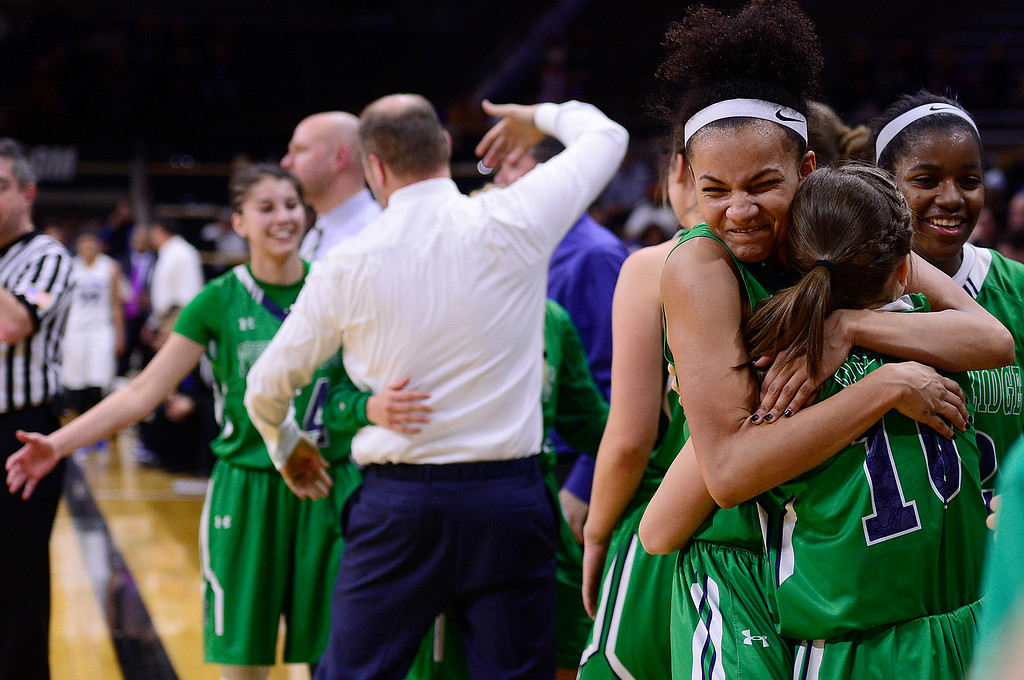 . Dallas Petties (21) of ThunderRidge hugs Mia Needles (10) of ThunderRidge  after coming off the court for the final time during the fourth quarter at the Coors Events Center on March 12, 2016 in Boulder, Colorado. ThunderRidge defeated Highlands Ranch 47-32 to win the Class 5A Colorado State Basketball Championship. (Photo by Brent Lewis/The Denver Post)