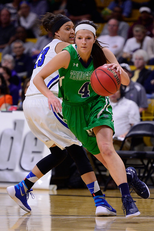 . Taylor Rusk (4) of ThunderRidge slips around the defense of Brianne Stiers (23) of Highlands Ranch during the first quarter at the Coors Events Center on March 12, 2016 in Boulder, Colorado. (Photo by Brent Lewis/The Denver Post)