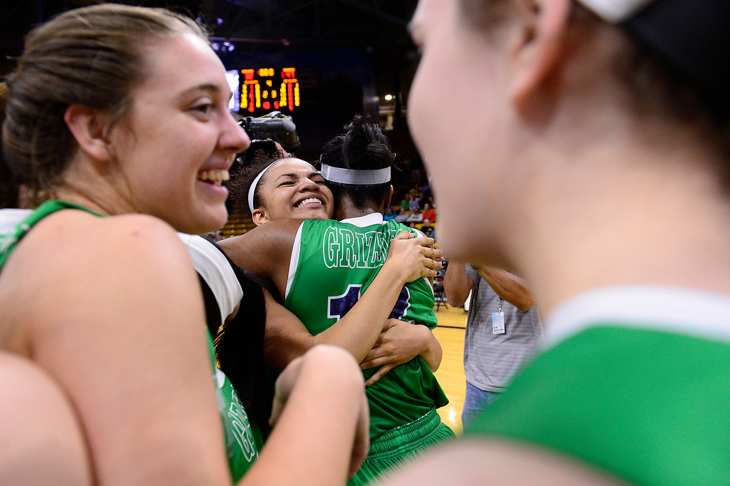. Dallas Petties (21) is hugged by Jaz\'myne Snipes (12) of ThunderRidge after they defeated Highlands Ranch at the Coors Events Center on March 12, 2016 in Boulder, Colorado. ThunderRidge defeated Highlands Ranch 47-32 to win the Class 5A Colorado State Basketball Championship. (Photo by Brent Lewis/The Denver Post)