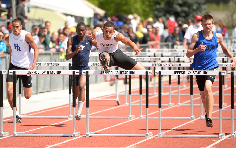. Travis Gordon, center, of Palmer High School, got the best time in the 5A qualifying 110m hurdles race during the Colorado High School State Track and Field Championships, May 15, 2014. Action will continue through Saturday at Jeffco Stadium in Lakewood. (Photo by RJ Sangosti/The Denver Post)
