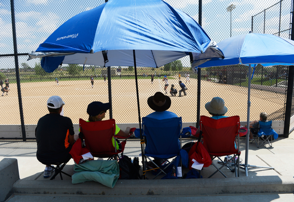. Girls softball fans enjoy a game under umbrellas at the Colorado Sparkler, Sparkler Junior & Fireworks girls fast pitch club softball tournament at the Aurora Sports Park Wednesday afternoon, July 02, 2014. The Colorado Sparkler & Fireworks, Sparkler Juniors, fast pitch softball tournament is one of the largest high school and junior girls fast pitch club tournaments in the country which is being played at several locations on the front range and features over 800 teams from across the country. (Photo By Andy Cross / The Denver Post)