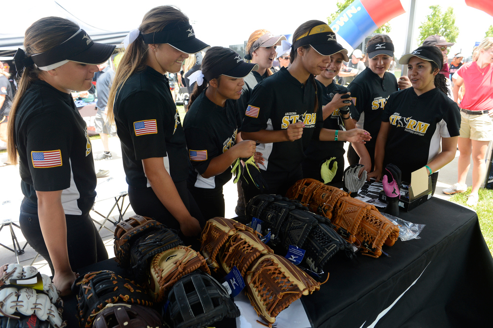 . Arizona Storm softball players check out batting gloves and softball gloves at the Mizuno booth at the Colorado Sparkler, Sparkler Junior & Fireworks girls fast pitch club softball tournament at the Aurora Sports Park Wednesday afternoon, July 02, 2014. The Colorado Sparkler & Fireworks, Sparkler Juniors, fast pitch softball tournament is one of the largest high school and junior girls fast pitch club tournaments in the country which is being played at several locations on the front range through July 06, 2014 that features over 800 teams from across the country. (Photo By Andy Cross / The Denver Post)