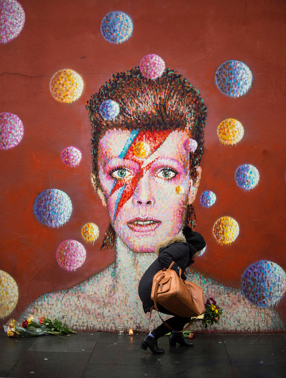 ". Flowers are left below a mural of David Bowie on the wall of a Morley\'s store in Brixton, London, the singer\'s birthplace, after the rock star died, Monday Jan. 11, 2016.  Bowie, the iconic and shape-shifting British singer whose illustrious career lasted five decade with hits like ""Fame,\"" \'\'Heroes\"" and \""Let\'s Dance,\"" died Sunday, Jan. 10, 2016,  after a battle with cancer. He was 69. (Anthony Devlin/PA via AP) UNITED KINGDOM OUT NO SALES NO ARCHIVE"